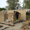photograph on site at pear tree farm with the bricklayer putting up the internal blockwork walls